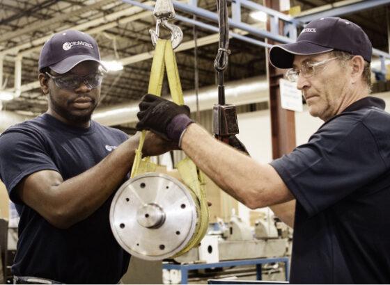 Men hoisting rotary die